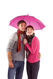 Couple standing underneath an umbrella