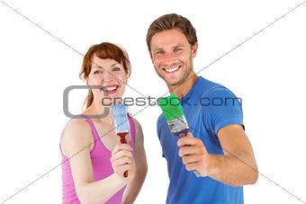 Couple both holding paint brushes