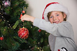 Child hanging up tree decorations