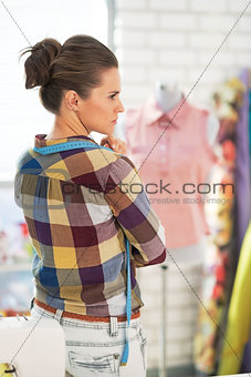 Portrait of thoughtful dressmaker woman in front of mannequin