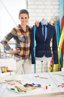 Portrait of tailor woman near mannequin wearing business suit