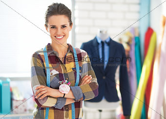 Portrait of happy tailor woman in front of mannequin wearing bus
