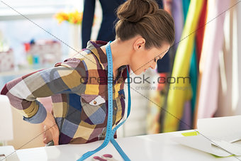 Portrait of tired tailor woman with back pain
