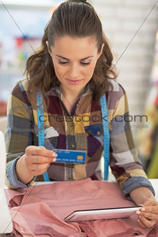 Portrait of tailor woman with credit card using tablet pc at wor