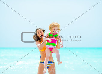Portrait of smiling mother and baby girl on beach