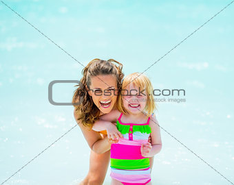 Portrait of smiling mother and baby girl at seaside