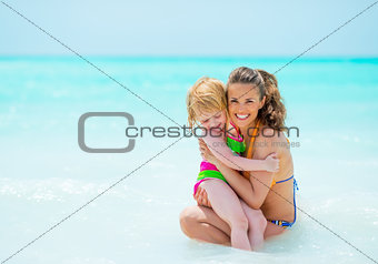 Portrait of mother and baby girl on sea shore