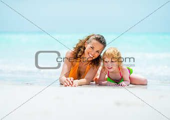 Portrait of mother and baby girl relaxing on sea coast