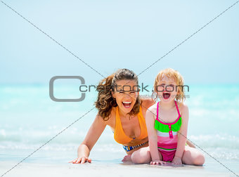 Portrait of cheerful mother and baby girl on sea shore