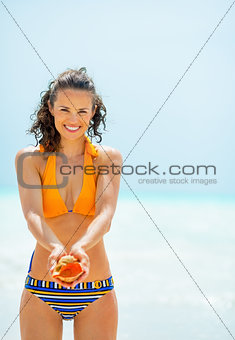 Portrait of happy young woman showing shell on beach