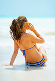 Young woman listening sound of sea in shell on sea coast. rear v