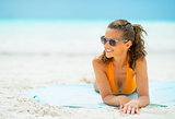 Smiling young woman in sunglasses laying on sea coast looking on