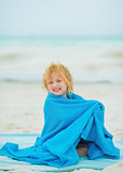 Smiling baby girl wraped in towel sitting on beach