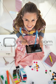 Portrait of happy tailor woman using tablet pc at work