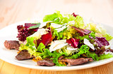Fresh salad with lettuce leaves, fried beef, beet, cheese