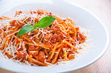 spaghetti bolognese on white plate with tomato sauce and basil leaves