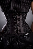 Back view of woman in black rose corset