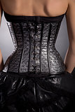 Rear view of woman in silver leather corset