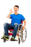 happy young man sitting on a wheelchair and ok gesture