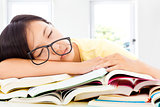 tired student girl with glasses sleeping on the books