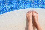 feet of a young woman on the edge of the pool