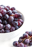 Dark grape in a bowl on white