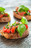 Italian tomato bruschetta with chopped vegetables, herbs and oil on grilled or toasted crusty ciabatta