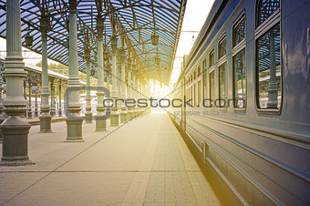 Trains stand at the station at sunrise time.