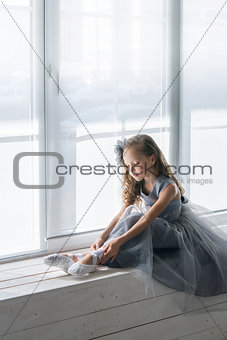 Little ballerina in gray dress puts on ballet shoes pointe front