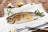 Two grilled trouts with fresh herbs and lemon pieces on wooden t