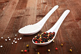 Salt and pepper on white spoons.