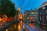Night city view of Amsterdam canal, church and bridge