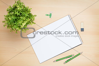 Blank notepad, pen and flower on wooden table