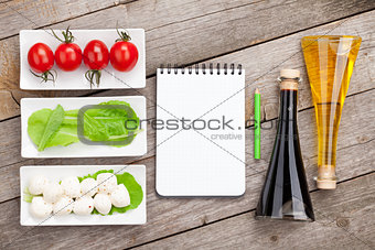 Tomatoes, mozzarella and green salad leaves with notepad for cop