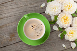 Coffee cup and white rose flowers