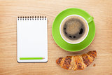 Cup of coffee, fresh croissant and notepad