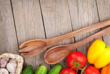 Fresh ripe vegetables and utensils on wooden table