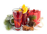Christmas mulled wine with spices, gift box and snowy fir tree