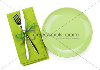 Fork with knife over towel and empty plate