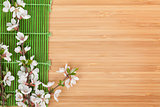Sakura branch over bamboo mat