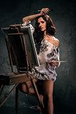 Sexy woman painting, studio shot