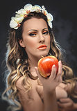 Beautiful seductive woman with apple, conceptual photo