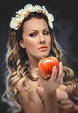 Beautiful seductive woman with apple, conceptual photo