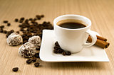 Cup of coffee with beans and truffles over wooden background