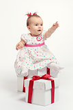 Adorable baby girl with two gift boxes