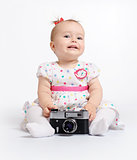 Adorable baby with retro camera over white background