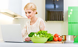 Young woman looking for a recipe on the laptop computer