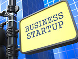 Business Startup. Signpost on Blue Background.