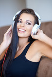 Happy tanned young woman enjoying her music