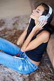 Woman relaxing on the floor listening to music